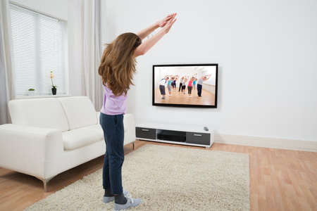 sofa television: Girl Looking At Television While Doing Exercise At Home Stock Photo