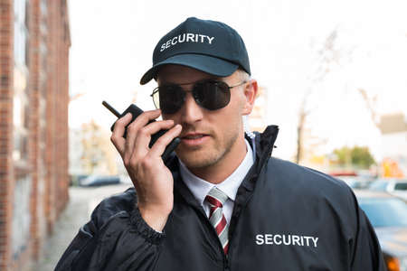 security uniform: Portrait Of Young Male Security Guard Talking On Walkie-talkie Stock Photo