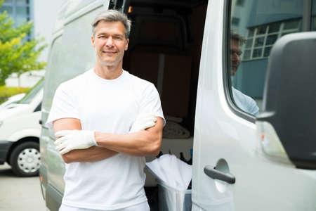 pintor: Pintor Hombre feliz con los brazos cruzados de pie delante de Van Foto de archivo