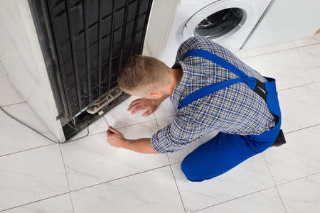 refrigerator kitchen: Young Male Repairman Making Refrigerator Appliance In Kitchen Room