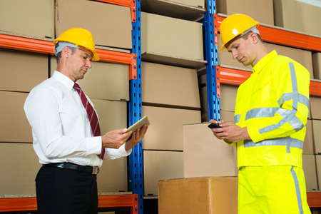 mobile: Businessman And Worker Using Digital Tablet And Mobile Phone In Warehouse