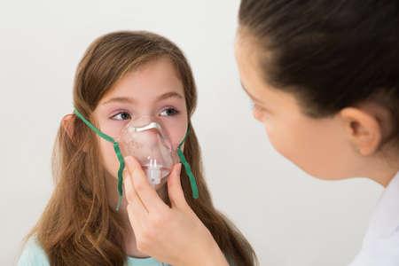 asthmatic: Medical Doctor Holding Inhaler Mask For Girl Breathing Stock Photo