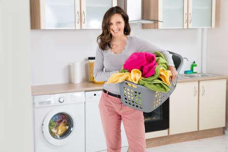 lavadora con ropa: Feliz mujer que lleva la cesta de lavadero en cocina Sala