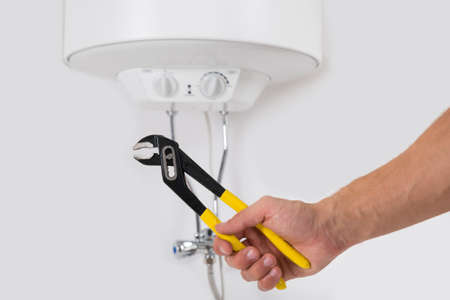 Close-up Person Hands Holding Wrench In Front Of Electric Boiler Attached On White Wall Stock Photo
