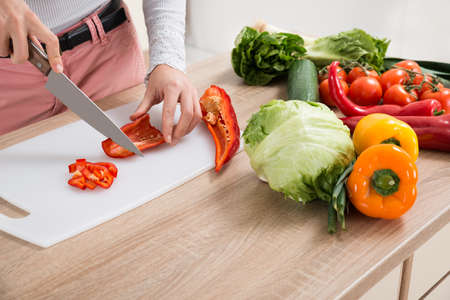 woman knife: Close-up Of Woman Chopping Chili Pepper With Knife At Home