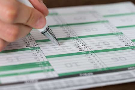 Close-up Of Person Hands Writing An Important Event On Calendar