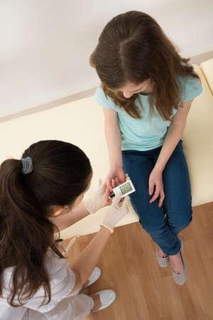 labcoat: Doctor In Labcoat Measuring Blood Sugar Level Of Girl With Glucometer
