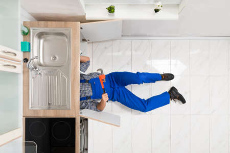 Worker Lying On Floor Repairing Kitchen Sink With Adjustable Wrench