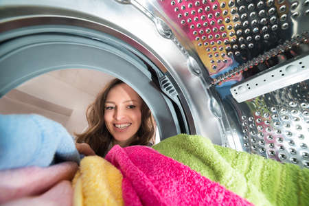 Close-up Of Happy Woman View From Inside The Washer With Clothes