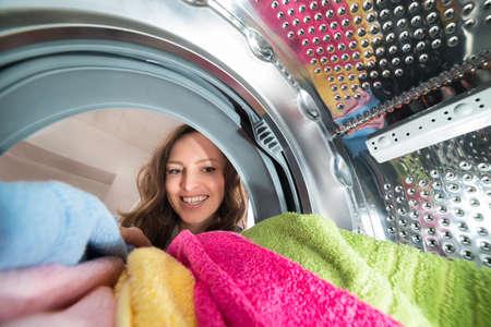 tambor: Primer plano de mujer de visión desde dentro de la lavadora con ropa Foto de archivo