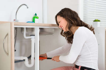 tightening: Woman Tightening Pipe Under Sink With Worktool At Home