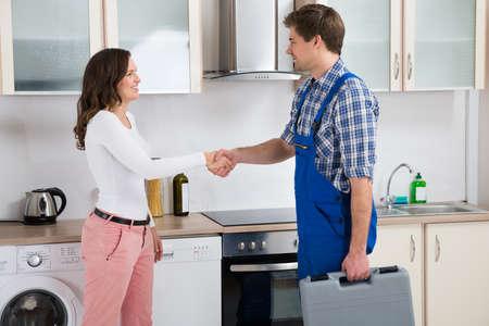 lavavajillas: Varón joven Reparador darle la mano a feliz mujer en la cocina