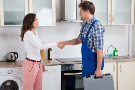 man machine: Young Male Repairman Shaking Hands With Happy Woman In Kitchen