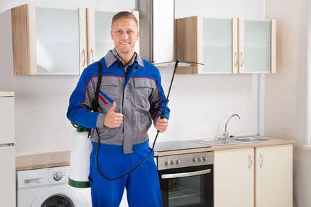 キッチン ルームで殺虫剤スプレーで若い幸せな害虫制御ワーカー