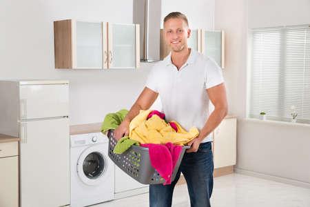 lavanderia: Joven hombre feliz con ropa multicolor en la cesta de lavadero en cocina americana