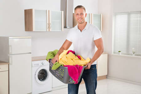 man laundry: Young Happy Man Carrying Multi-colored Clothes In Laundry Basket In Kitchen Room Stock Photo