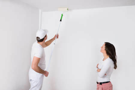Young Woman Looking At Painter Painting White On Wall In House Stock Photo