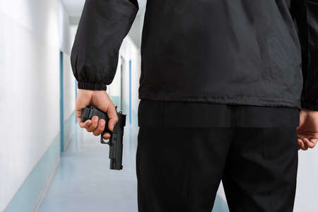 hitman: Close-up Of Security Guard Holding Black Pistol In Hands