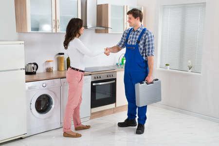 dando la mano: Varón joven Reparador darle la mano a feliz mujer en la cocina