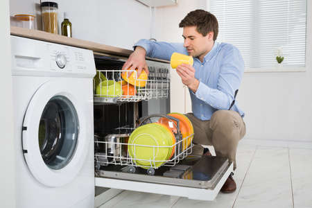 arranging: Young Happy Man Arranging Dishes In Dishwasher In Modern Kitchen Stock Photo