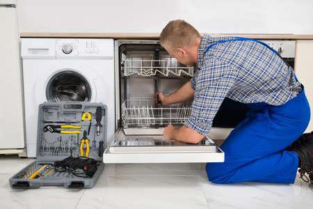 gospodarstwo domowe: Młody człowiek w kombinezonie z Toolbox naprawianie Zmywarka