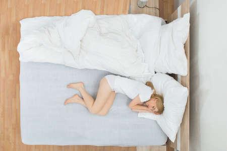 vysoký úhel pohledu: Mladá žena spí na bílé posteli v ložnici Reklamní fotografie