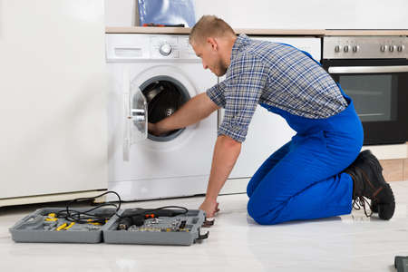 Male Worker With Toolbox Repairing Washing Machine In Kitchen Reklamní fotografie