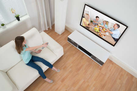 Girl Holding Remote Control In Front Of Television In Living Room photo