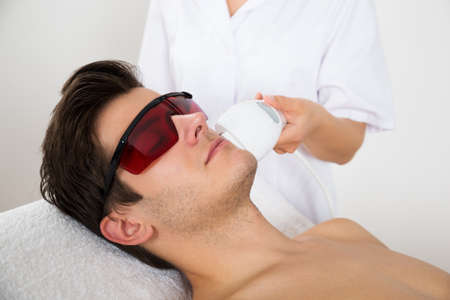 treatment: Young Man Receiving Laser Hair Removal Treatment At Beauty Center Stock Photo