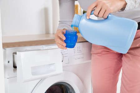 青いボトル キャップで洗剤を注ぐ女性の手のクローズ アップ 写真素材