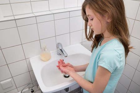 lavandose las manos: Niña de lavarse las manos con jabón en fregadero cuarto de baño