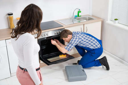 Woman Looking At Male Worker Repairing Oven Appliance In Kitchen Room Stock Photo
