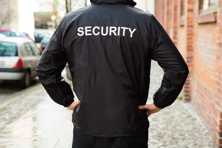 Close-up Of Male Security Guard Wearing Black Jacket Foto de archivo
