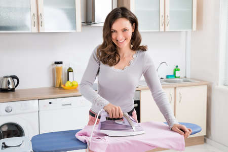 woman ironing: Happy Woman Ironing Cloth With Electric Iron In Kitchen Stock Photo