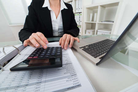 calculating: Close-up Of Businesswoman Calculating Invoice With Calculator Stock Photo