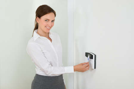 identification: Young Businesswoman Smiling While Inserting Keycard In Door Security System