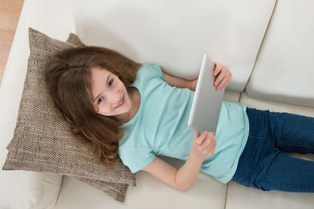 digital device: High Angle View Of Girl Lying On Sofa Using Digital Tablet In Living Room