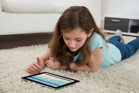 media gadget: Girl Lying On Carpet Watching Video On Digital Tablet In Living Room