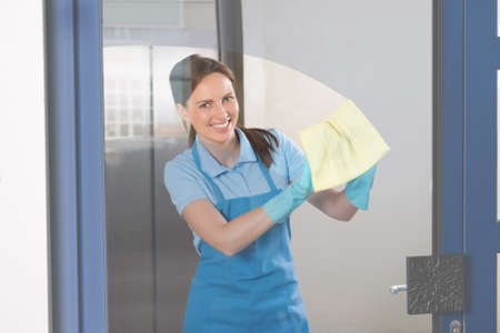 Young Happy Female Janitor Cleaning Glass With Rag