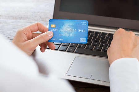 bank transfer: Close-up Of Businesswoman Hands Using Credit Card And Laptop At Desk