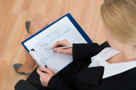 High Angle View Of Businesswoman Filling Blank Weekly Time Sheet In Office Stock Photo