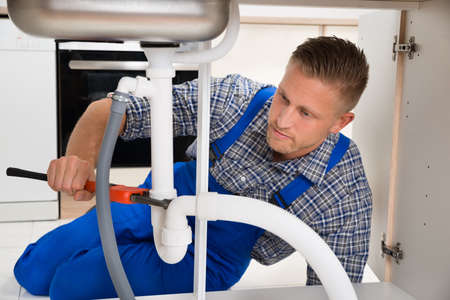 plomeria: Fontanero sexo masculino que repara el fregadero blanco de tuberías en la habitación Cocina