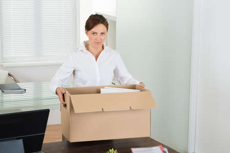 Young Businesswoman Packing Her Belongings In Box At Desk Stock Photo