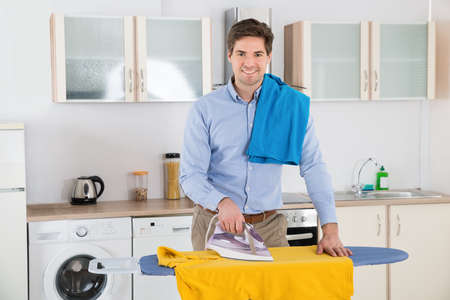 iron: Young Man Smiling While Ironing Clothes On Ironing Board At Home Stock Photo