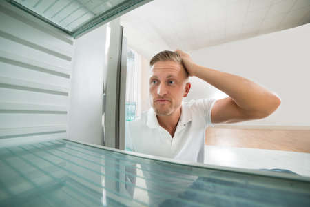 refrigerator kitchen: Portrait Of Hungry Man Looking In Empty Refrigerator In Kitchen Stock Photo