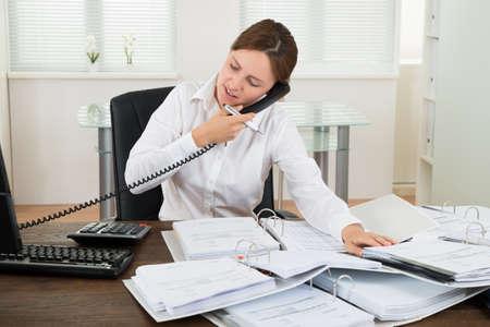 Jeune femme d'affaires parle au téléphone tout en faisant Comptabilité Dans Office