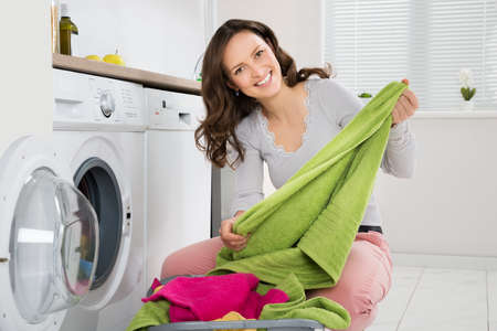 machine à laver: Jeune femme heureuse blanchiment vêtements dans la laveuse électronique Banque d'images