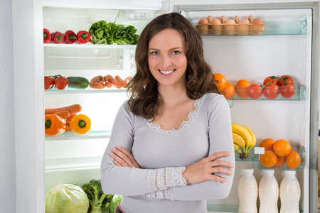 veggies: Young Happy Woman With Armcrossed In Front Of Open Fridge With Healthy Food