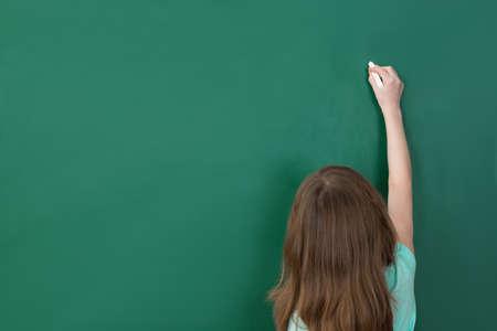 personas de espalda: Escritura de la muchacha con tiza en la pizarra verde en el aula Foto de archivo
