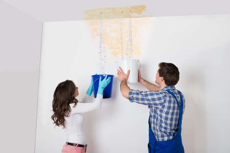 leaking: Young Woman And Repairman With Bucket Collecting Water From Damaged Ceiling